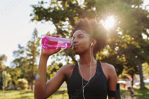Valokuvatapetti Fitness athlete young african american woman listening to music on earphones dri