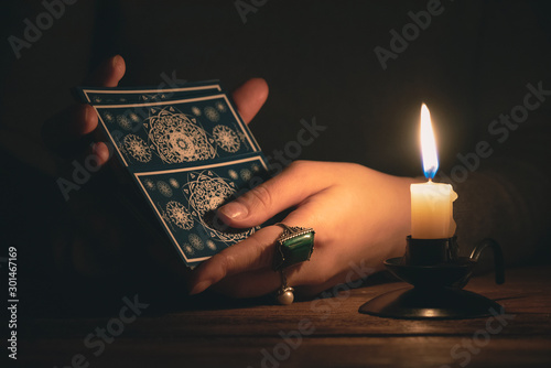 Fortune teller reading a future by tarot cards in the light of candle concept Fototapeta