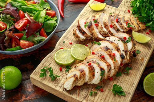 Canvas Print Homemade Grilled Chicken Breast in lime sauce with herbs on wooden board