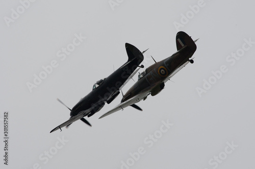 Photo Spitfire and Hurricane world war 2 fighters in close turning formation with ligh