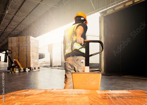 Fotografía Warehouse worker unloading pallet shipment boxes into cargo container