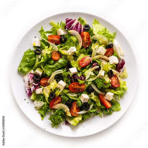 Canvas Print Fresh greek salad on a plate on white background