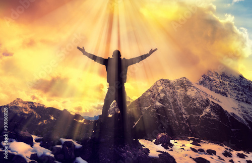 Obraz na płótnie Man Praying With Arms Open On Epic Mountain Top Summit With Light Shining With A