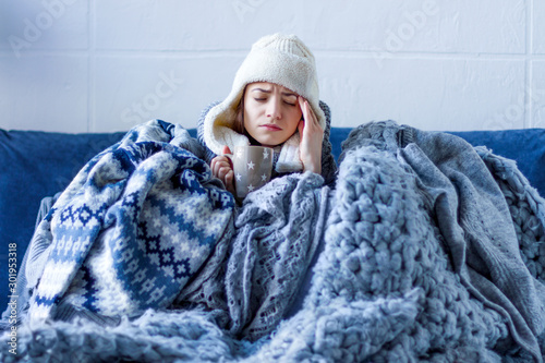 Sick exhausted girl in white warm hat wrapped herself in scarves and blankets is sitting in bed Fototapeta