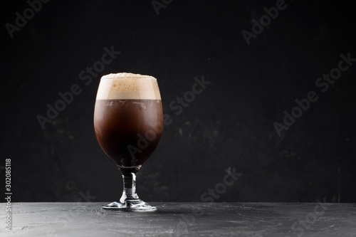 Photo Dark cold  foamy beer in classic pub glass on black background