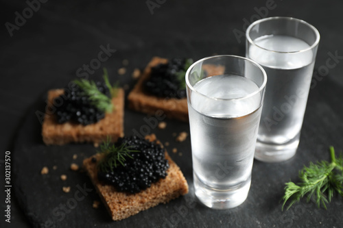 Cold Russian vodka and sandwiches with black caviar on table, closeup Fototapeta