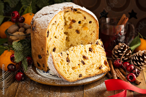 Obraz na plátně Traditional Christmas panettone with dried fruits and orange zest on rustic back