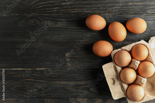 Tableau sur Toile Chicken eggs in carton box on wooden background, space for text