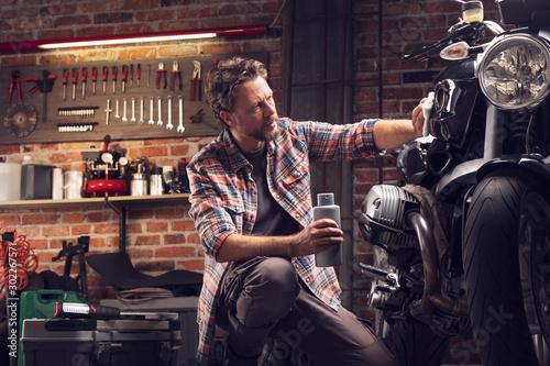 Canvas Print Man polish motorcycle in garage