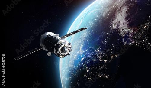 Fotografie, Obraz Cargo spaceship on orbit of the Earth planet