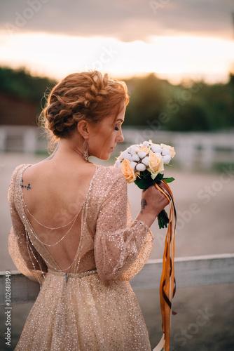 Obraz na płótnie Portrait of a bride sniffing a bouquet in the sunset light
