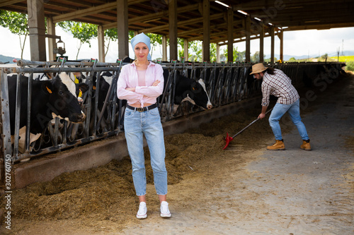 Fotografija Young female breeder in cowshed