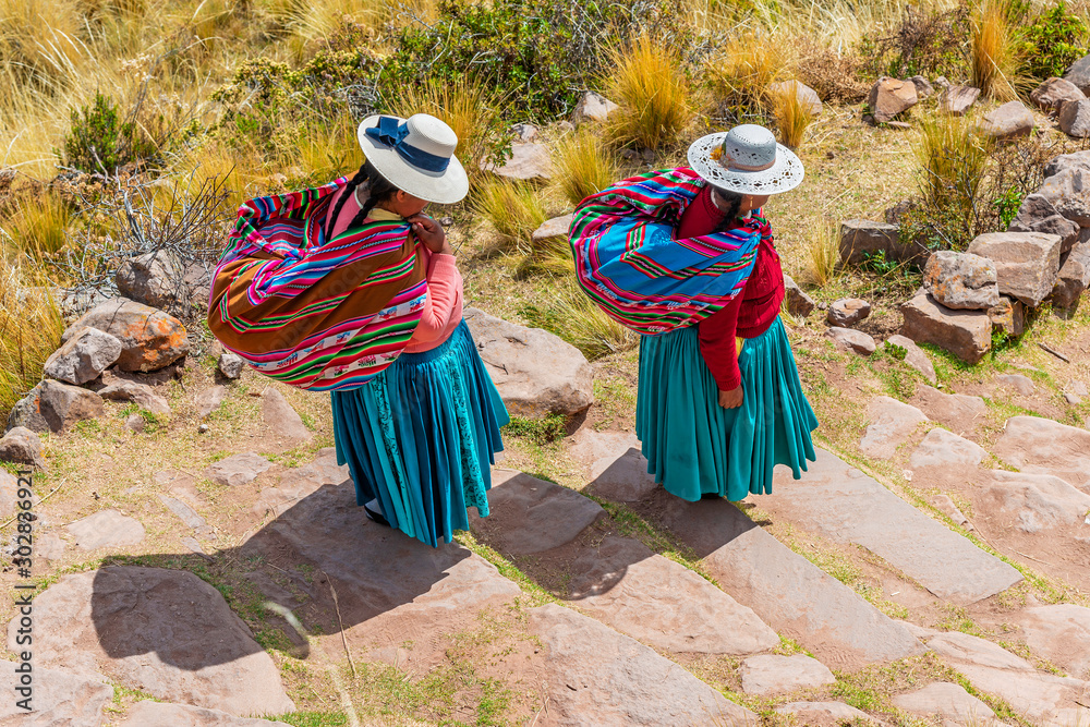 Two Quechua indigenous women in traditional clothing and textile walking down the steps on Taquile island by the Titicaca Lake, Puno, Peru. <span>plik: #302836921 | autor: SL-Photography</span>
