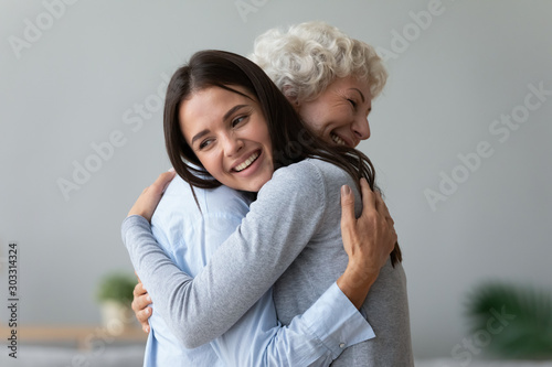 Photo Happy young granddaughter embracing hugging old retired grandmother cuddling