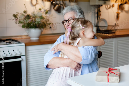 Wallpaper Mural Grandmother is hugging child girl in cozy kitchen at home