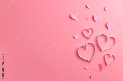 Composition for Valentine's Day February 14th. Delicate pink background and pink hearts cut out of paper. Greeting card. Flat lay, top view, copy space.