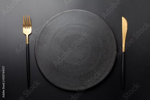 Obraz na plátně Empty black plate with fork and knife on black background