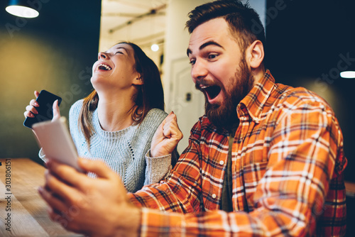 Excited male and female hipsters rejoice in winning an internet lottery made bets on website on modern smartphone Fototapeta