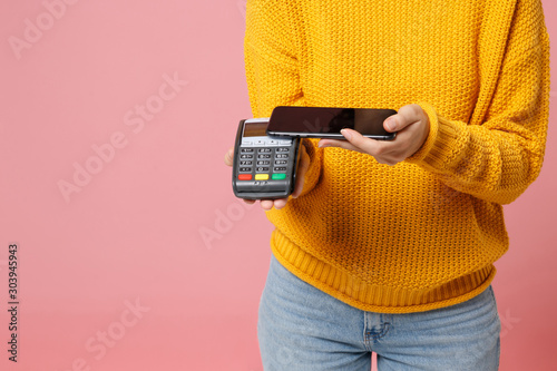 Cropped image of woman in yellow sweater posing isolated on pink background Fototapeta