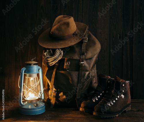 Fotografia Vintage nomad's gear arranged on old wooden floor inside of remote cabin