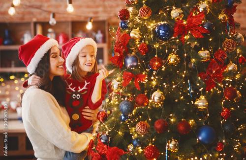 Fotografia Little girl enjoying Christmas tree with her mom