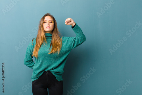 Fotografia young pretty woman feeling serious, strong and rebellious, raising fist up, prot