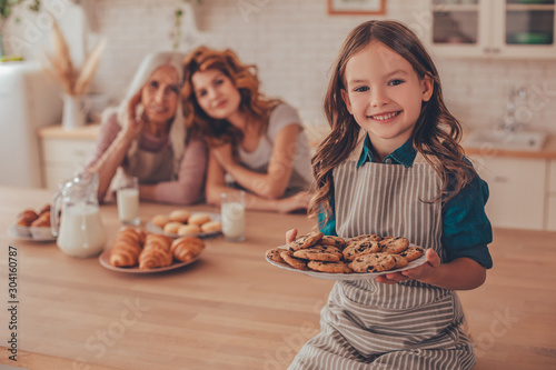 Fotografie, Obraz cheerful girl holding plate with biscuits and looking at the camera with mother