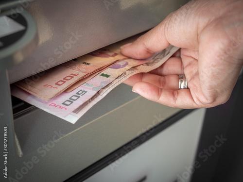 Fototapeta Hand receiving cash money from ATM machine.