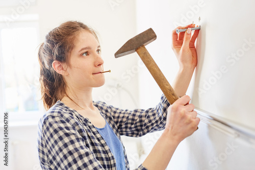 Fototapeta Young woman as a handyman with hammer