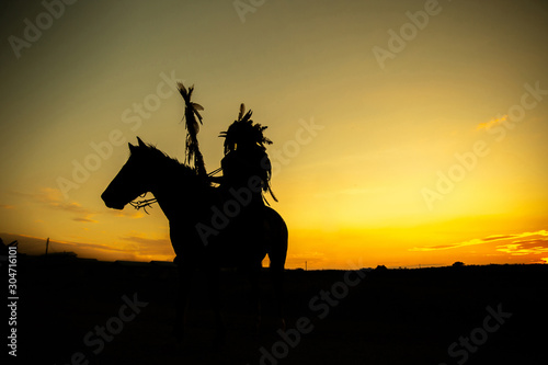Fotografia The Indians are riding a horse and spear ready to use In light of the Silhouette