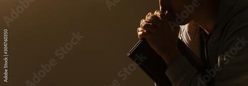 Fotografie, Obraz Religious young man praying to God on dark background, black and white effect