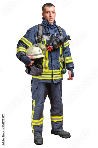 Canvas Print A young brave fireman in a fireproof uniform stands and looks at the camera with a helmet in his hands