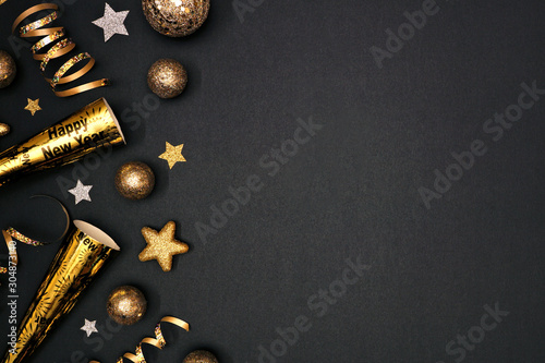 New Years Eve side border of glittery gold stars, streamers, decorations and noisemakers Fototapet
