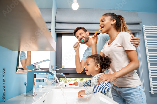 Photo Mother, father and daughter brushing teeth in bathroom