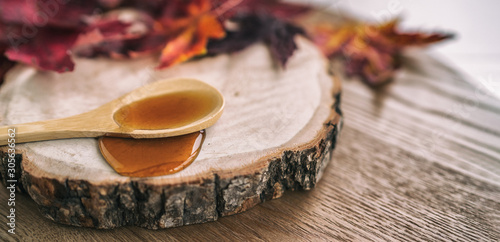 Fototapeta Maple syrup sugar shack cabane a sucre restaurant from Quebec farm maple tree sap famous sweet liquid dripping from wooden spoon on wood log rustic sugar shack banner panoramic with red leaves