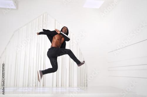 Elegant black man dancer in black clothes jumping in a bright room Fotobehang