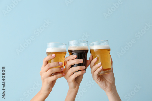 Fotografia Hands with glasses of beer on color background