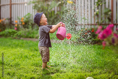 Mom and boy child water the garden together joke
