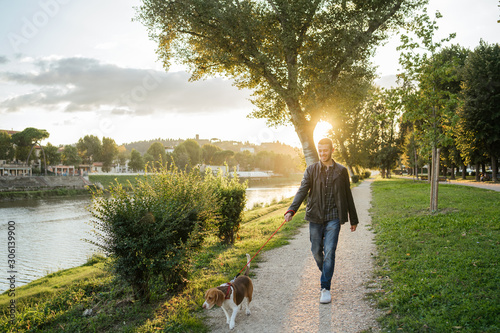 Photo Young man takes his beloved dog for a walk in the park at sunset - Millennial in