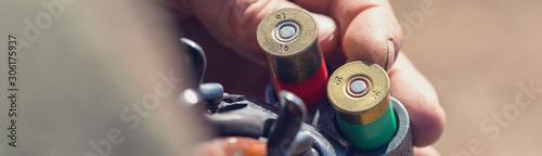 Obraz na plátně Close up of hunter loading shotgun,