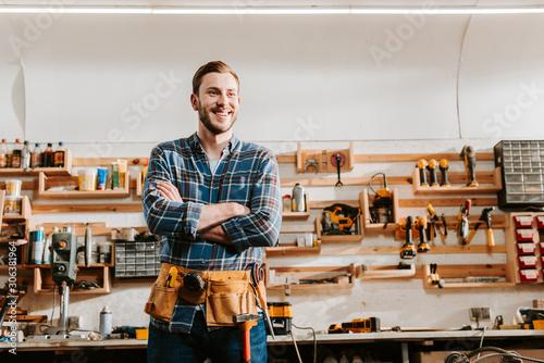 Billede på lærred cheerful carpenter in apron standing with crossed arms