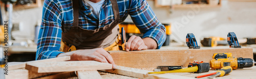 Photo panoramic shot of carpenter touching wooden dowel