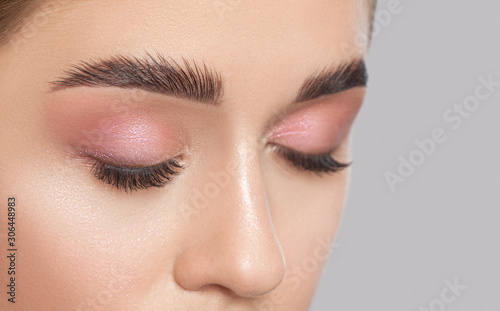 Beautiful young woman with long eyelashes, beautiful fresh nude make-up, thick eyebrows and with clean skin in a beauty salon Fototapeta
