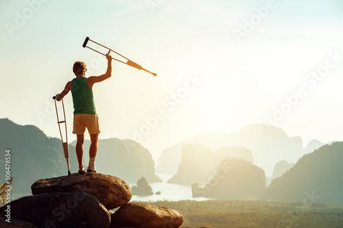 Obraz na płótnie Disabled man with crutches stands on big rock