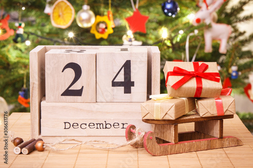 Fotografering Date 24 December on calendar, wrapped gifts and christmas tree with decoration,