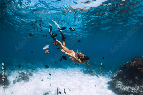 Photo Freediver girl with fins glides over sandy bottom with fishes in blue ocean