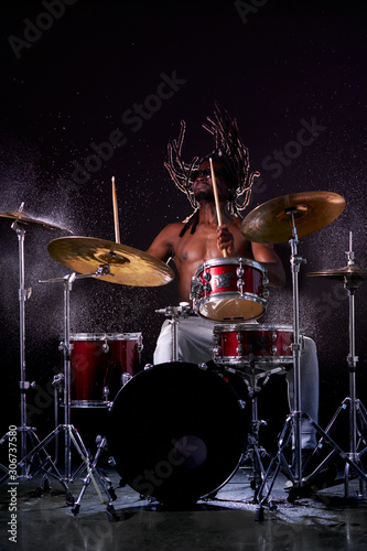 Fotografie, Obraz Portrait of african man playing on drums and cymbals, wearing eyeglasses and holding sticks