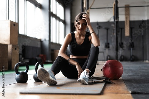 Young woman sitting on floor after her workout and looking down. Female athlete taking rest after fitness training