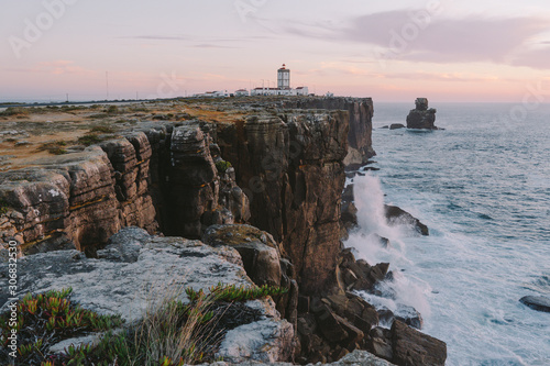 Canvas Print Lighthouse on the edge of a cliff big ocean waves crash on a rock Peniche Portug