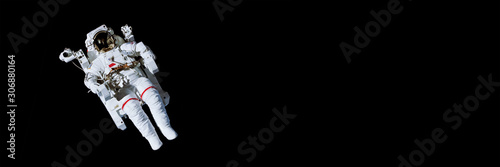 Stampa su Tela Astronaut with a jetpack isolated on black panoramic background with copy space